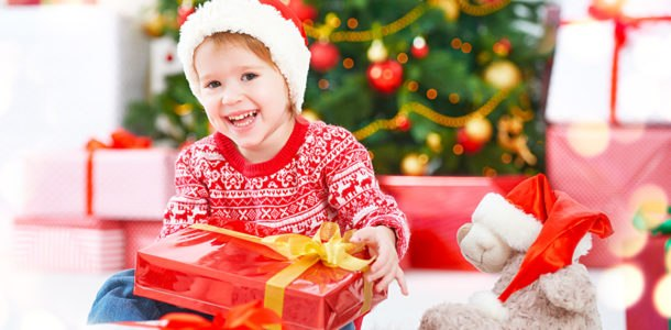 мальчик с подарком возле елки