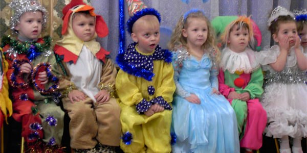 дети в костюмах сидят на лавке