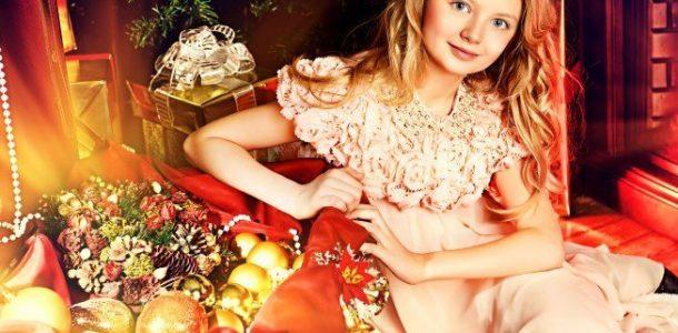 девочка в платье сидит на стуле возле новогодних шариков
